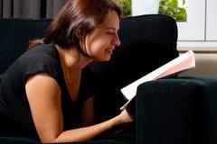 Donna che legge uno scomparto fotografia stock