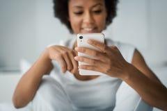 Donna che manda un sms con il suo smartphone fotografie stock libere da diritti