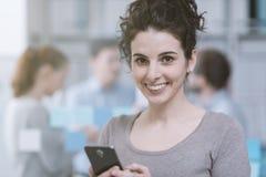 Donna che manda un sms con il suo smartphone nell'ufficio fotografie stock