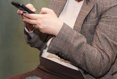Donna che manda un sms su uno smartphone Immagini Stock Libere da Diritti