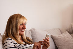 Donna che manda un sms sul sofà Fotografie Stock