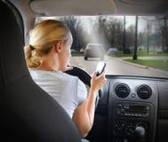 Donna che manda un sms sul telefono e che conduce automobile Fotografia Stock