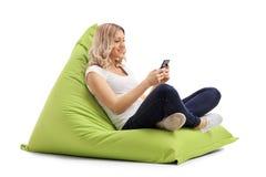 Donna che manda un sms sul telefono messo sul beanbag Immagini Stock Libere da Diritti