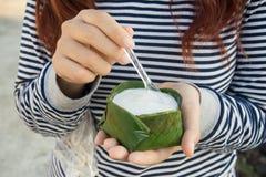 Donna che mangia budino con la guarnizione della noce di cocco Fotografie Stock Libere da Diritti