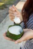 Donna che mangia budino con la guarnizione della noce di cocco Immagine Stock Libera da Diritti