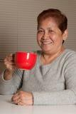Donna che mangia caffè Immagini Stock