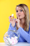 Donna che mangia caramella gommosa e molle Fotografia Stock