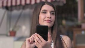 Donna che mangia dessert e che per mezzo del suo telefono al caffè di aria aperta archivi video