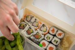 Donna che mangia edamame, salmone, surimi, cetriolo ed avocado Maki ed interno - fuori sushi di California con la salsa di soia,  immagini stock