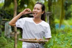 Donna che mangia gli insetti fritti Immagine Stock