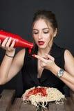 Donna che mangia gli spaghetti alla tavola di legno Immagini Stock