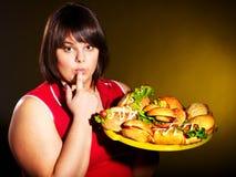 Donna che mangia hamburger. Fotografia Stock