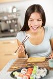 Donna che mangia i bastoncini della tenuta di maki dei sushi Immagini Stock Libere da Diritti