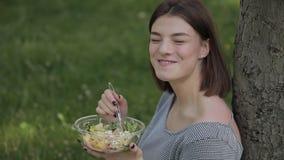 Donna che mangia insalata fresca che si siede al parco di estate archivi video