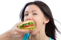 Donna che mangia l'hamburger non sano saporito degli alimenti a rapida preparazione Fotografia Stock Libera da Diritti