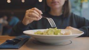 Donna che mangia l'insalata di caesar in un caffè video d archivio