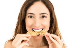 Donna che mangia la barra di energia Immagini Stock