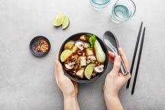 Donna che mangia la minestra vegetariana asiatica del tofu in ciotola immagine stock libera da diritti