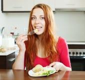 Donna che mangia le patate a casa Immagine Stock