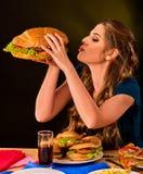 Donna che mangia le patate fritte ed hamburger con pizza Fotografia Stock Libera da Diritti