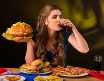 Donna che mangia le patate fritte ed hamburger sulla tavola Immagini Stock Libere da Diritti