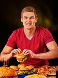 Donna che mangia le patate fritte ed hamburger sulla tavola Fotografie Stock