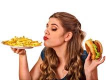 Donna che mangia le patate fritte ed hamburger sulla tavola Immagini Stock