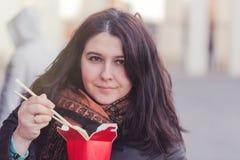Donna che mangia lo spuntino asiatico dell'alimento all'aperto nel parco con i bastoni Fotografie Stock