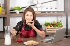 Donna che mangia pane tostato con l'inceppamento di fragola immagini stock