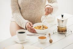 Donna che mangia prima colazione Immagini Stock