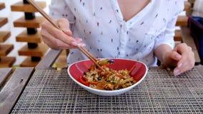 Donna che mangia riso con le verdure in alto reastaurant e vicino asiatico archivi video