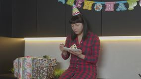 Donna che mangia torta di compleanno da solo in cucina domestica archivi video
