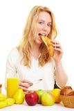 Donna che mangia un croissant fotografia stock libera da diritti