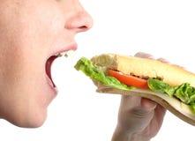 Donna che mangia un panino Fotografie Stock Libere da Diritti