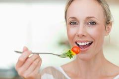 Donna che mangia una certa insalata Fotografia Stock