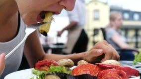 Donna che mangia una forcella con le verdure arrostite con il primo piano fresco dell'insalata nell'aria aperta di estate archivi video