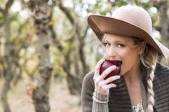 Donna che mangia una mela nel legno. Fotografia Stock