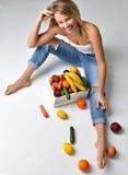 Donna che mangia vicino alla scatola con le verdure organiche fresche e la frutta Fotografie Stock Libere da Diritti