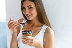 Donna che mangia yogurt, le bacche e farina d'avena per la prima colazione sana Immagini Stock Libere da Diritti