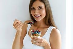 Donna che mangia yogurt, le bacche e farina d'avena per la prima colazione sana Fotografia Stock