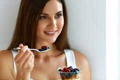 Donna che mangia yogurt, le bacche e farina d'avena per la prima colazione sana Immagine Stock Libera da Diritti