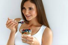 Donna che mangia yogurt, le bacche e farina d'avena per la prima colazione sana Immagine Stock