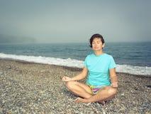 Donna che medita alla spiaggia Fotografie Stock Libere da Diritti