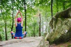 Donna che medita nella posa del loto, facente yoga su roccia fotografia stock libera da diritti