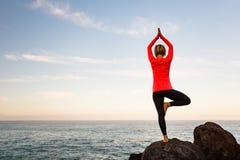 Donna che medita nella posa dell'albero di vrksasana di yoga Fotografia Stock