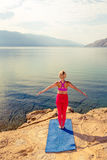 Donna che medita nella posa dell'albero di yoga al mare ed alle montagne Fotografia Stock Libera da Diritti
