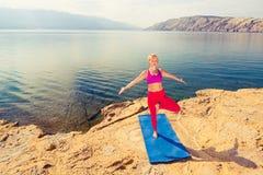 Donna che medita nella posa dell'albero di yoga al mare ed alle montagne Immagini Stock