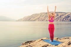 Donna che medita nella posa dell'albero di yoga al mare ed alle montagne Immagini Stock Libere da Diritti