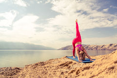 Donna che medita nella posa di yoga al mare ed alle montagne Fotografia Stock