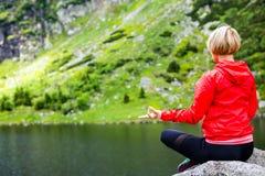 Donna che medita nella posa di yoga davanti al lago della montagna Immagine Stock